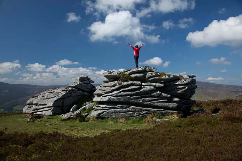 Walker on the granite tor of Fitzwilliam's Seat, near the summit of Knocknagun, Dublin Mountains, County Dublin, Ireland.