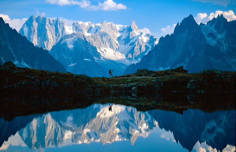 Walker and the Chamonix Aiguilles reflected in Lac des Cheserys, French Alps, France.