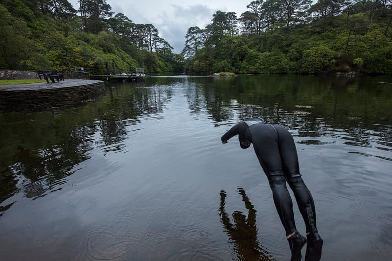 Swimmer diving into the Blue Pool, Glengarriff, County Cork, Ireland.