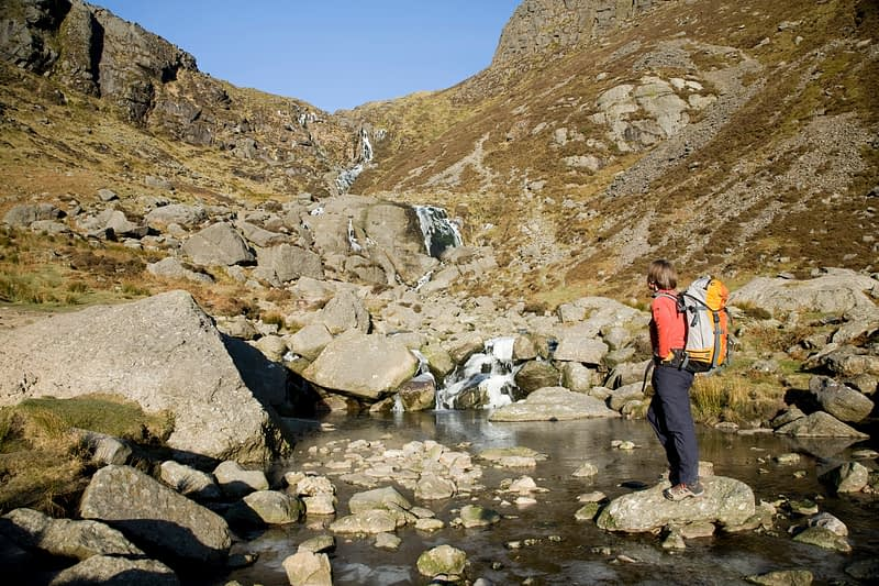 Walker beneath Mahon Falls, Comeragh Mountains, Co Waterford, Ireland.