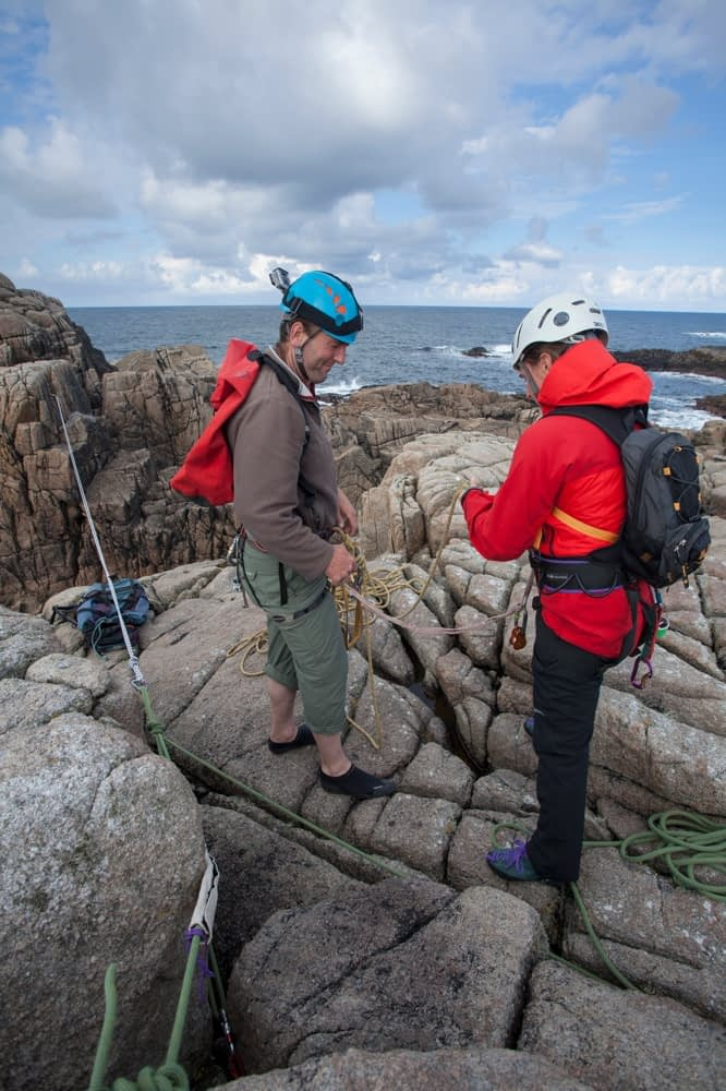 Rock climbers preparing a tyrolean traverse, County Donegal, Ireland.
