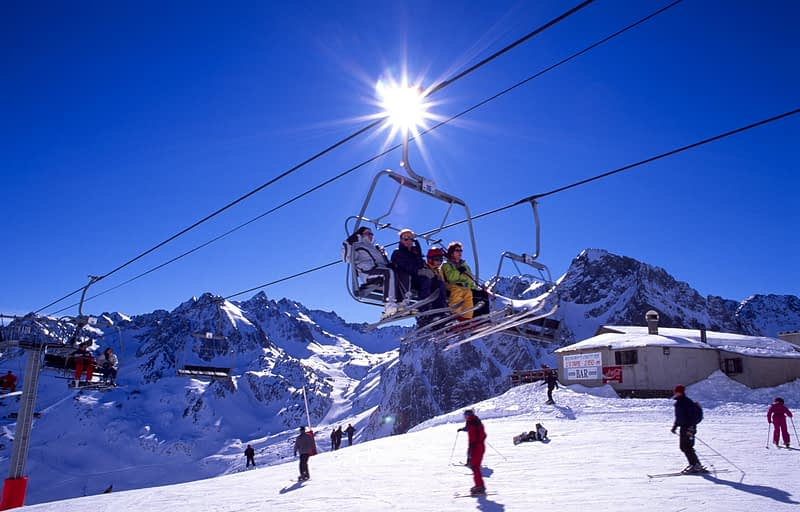 Skiers and chairlift on the slopes of La Mongie, French Pyrenees, France.