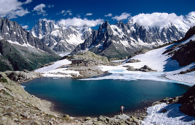 Walker looking over Lac Blanc and the Chamonix Aiguilles, French Alps, France.