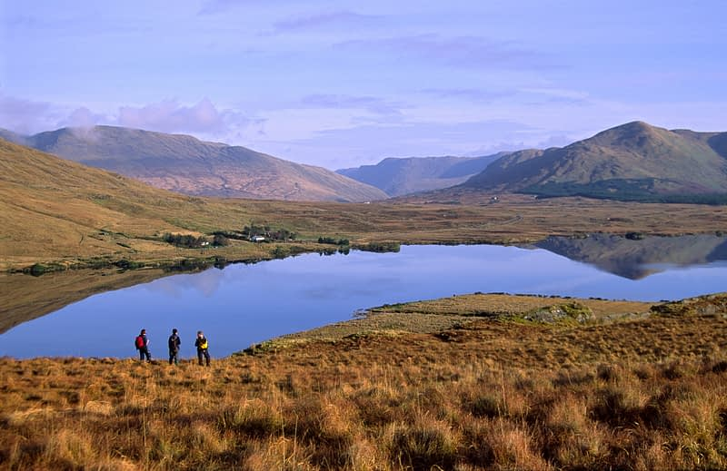 Walkers on the shore of Lough Fee, Connemara, Co Mayo, Ireland.