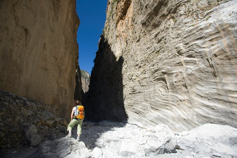 Hiker beneath the Iron Gates, Samaria Gorge, Samaria National Park, Crete, Greece.