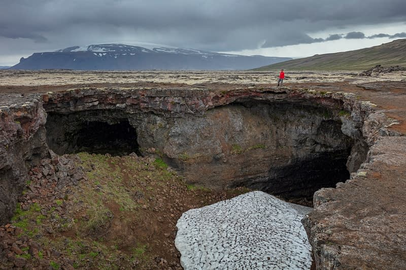 Person beside the entrance to Sturtshellir lava tube. Husafell, Sudhurland, Iceland.