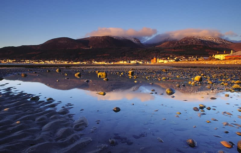Beach reflections of Newcastle and the Mourne Mountains, Co Down, Northern Ireland.