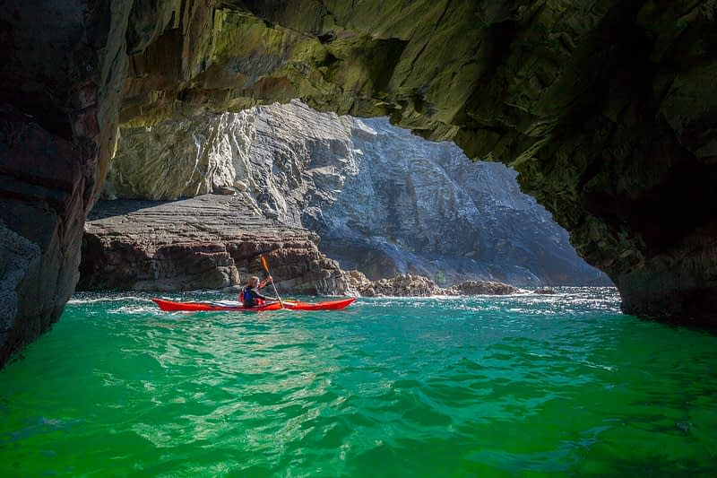 Sea kayaker exploring a cave near Glencolmcille, County Donegal, Ireland.
