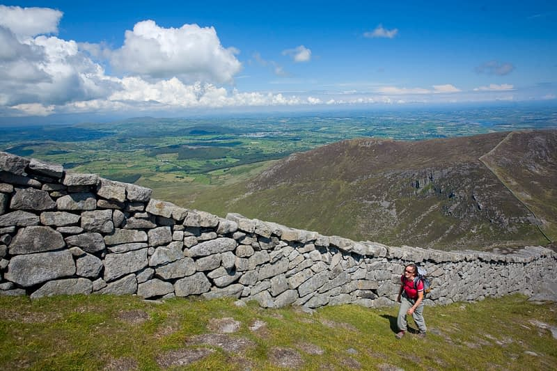 Walker beside the Mourne Wall on the ascent of Slieve Bearnagh, Mourne Mountains, Co Down, Northern Ireland.