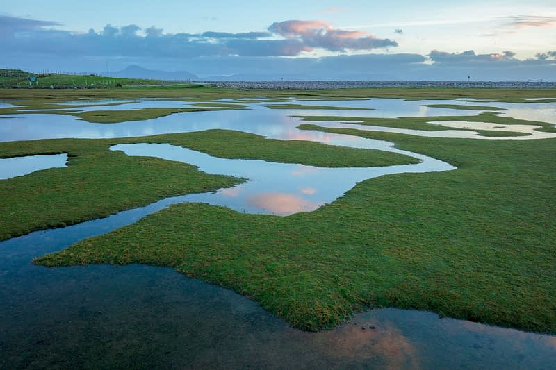 Reflection of evening sky in saltmarsh at high tide, Mulranny, County Mayo, Ireland.
