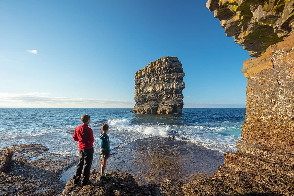People admiring Dun Briste sea stack from the shore beneath Downpatrick Head. County Mayo, Ireland.