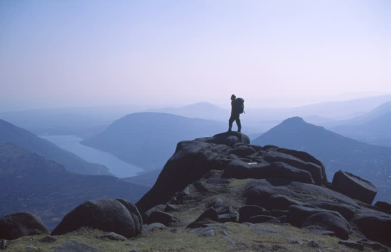 Walker silhouetted on the summit of Slieve Bearnagh, Mourne Mountains, Co Down, Northern Ireland.