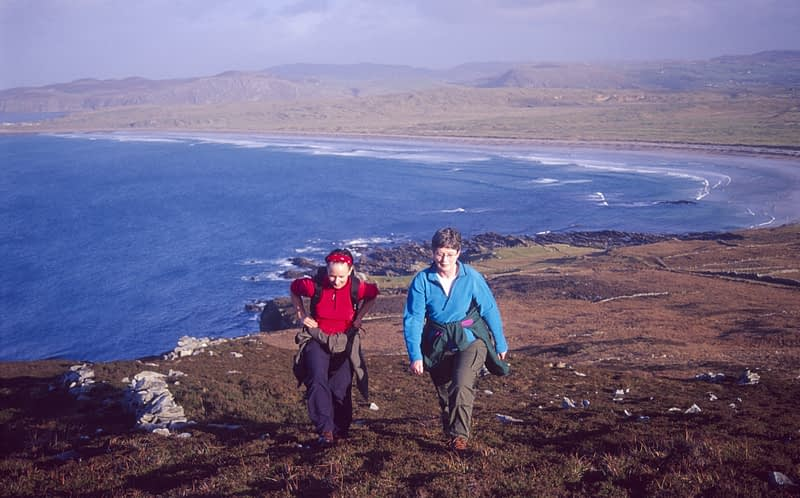 Walkers climbing Binnion above Pollan Bay, Inishowen, Co Donegal, Ireland.