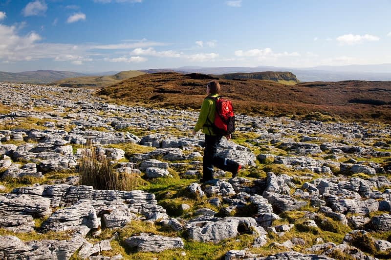 Walker crossing limestone pavement, Keelogyboy Mountain, Co Leitrim, Ireland.
