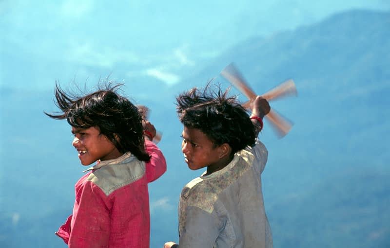 Tharu children playing with paper windmills, Western Nepal.