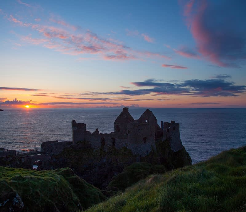 Sunset over Dunluce Castle, Causeway Coast, County Antrim, Northern Ireland.