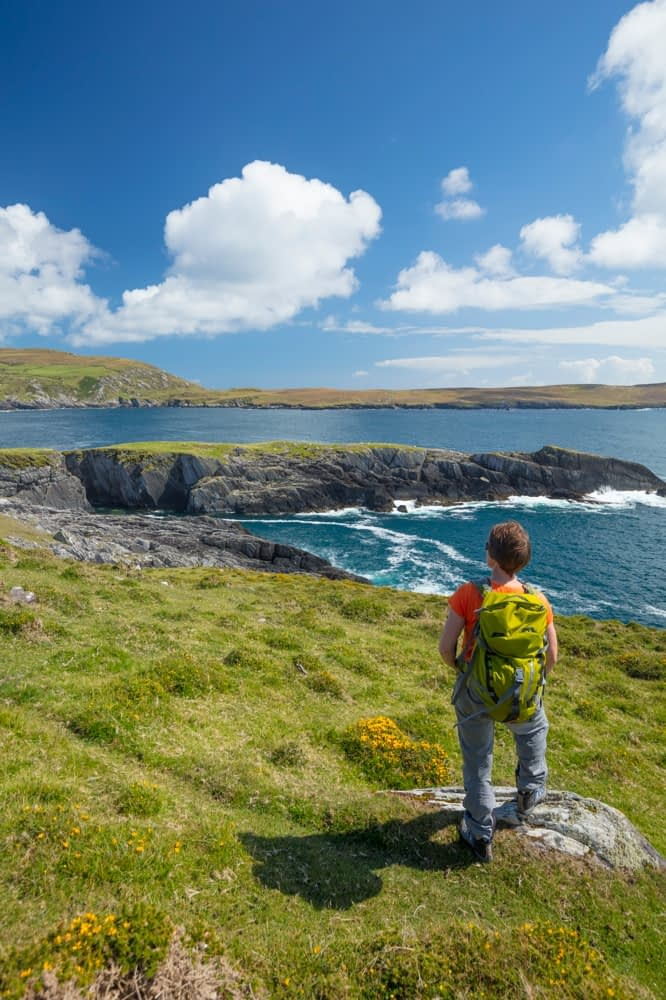 Hiker looking to Illanebeg islet, Dursey Island, Beara Peninsula, County Cork, Ireland.