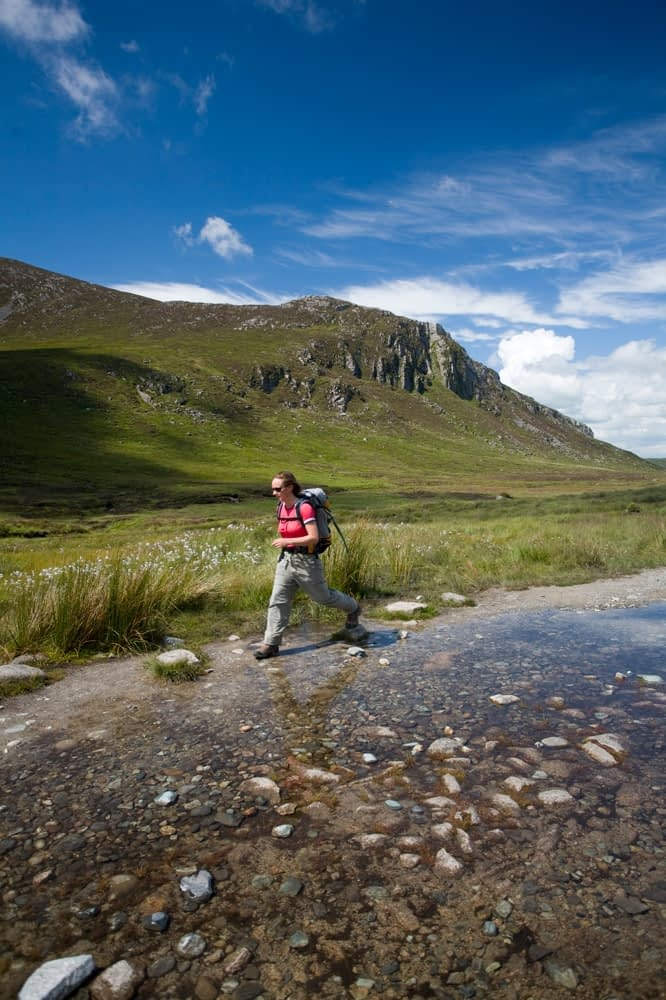 Walker passing a pool on the Trassey Track, Mourne Mountains, Co Down, Northern Ireland.
