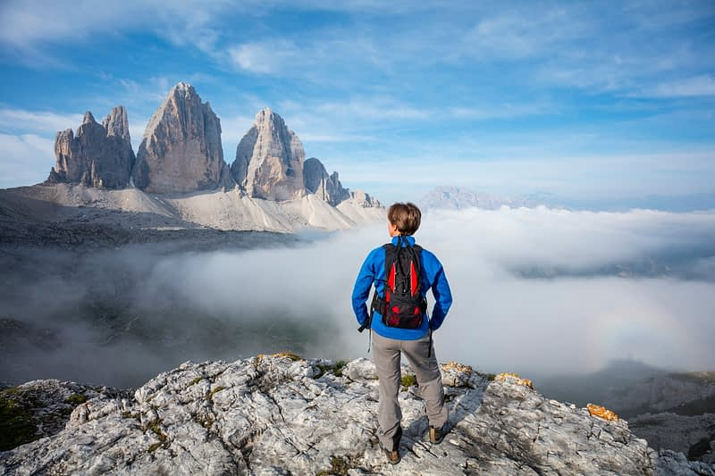 Hiker and morning cloud beneath Tre Cime di Lavaredo, Sexten Dolomites, South Tyrol, Italy.
