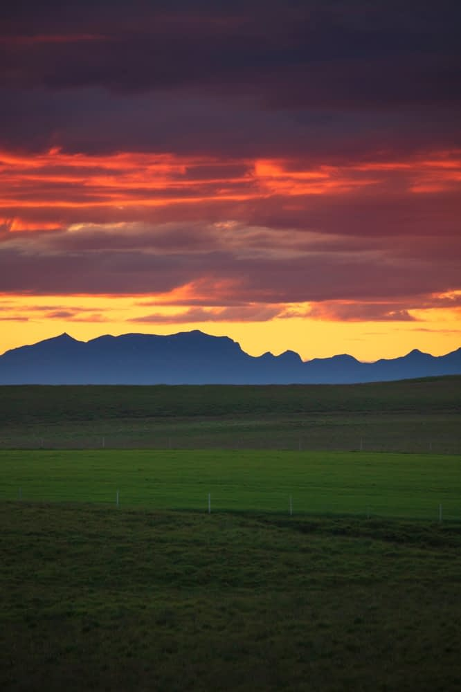 Sunset over grassy pastures beneath the Fjallabak mountains. Hella, Sudhurland, Iceland.