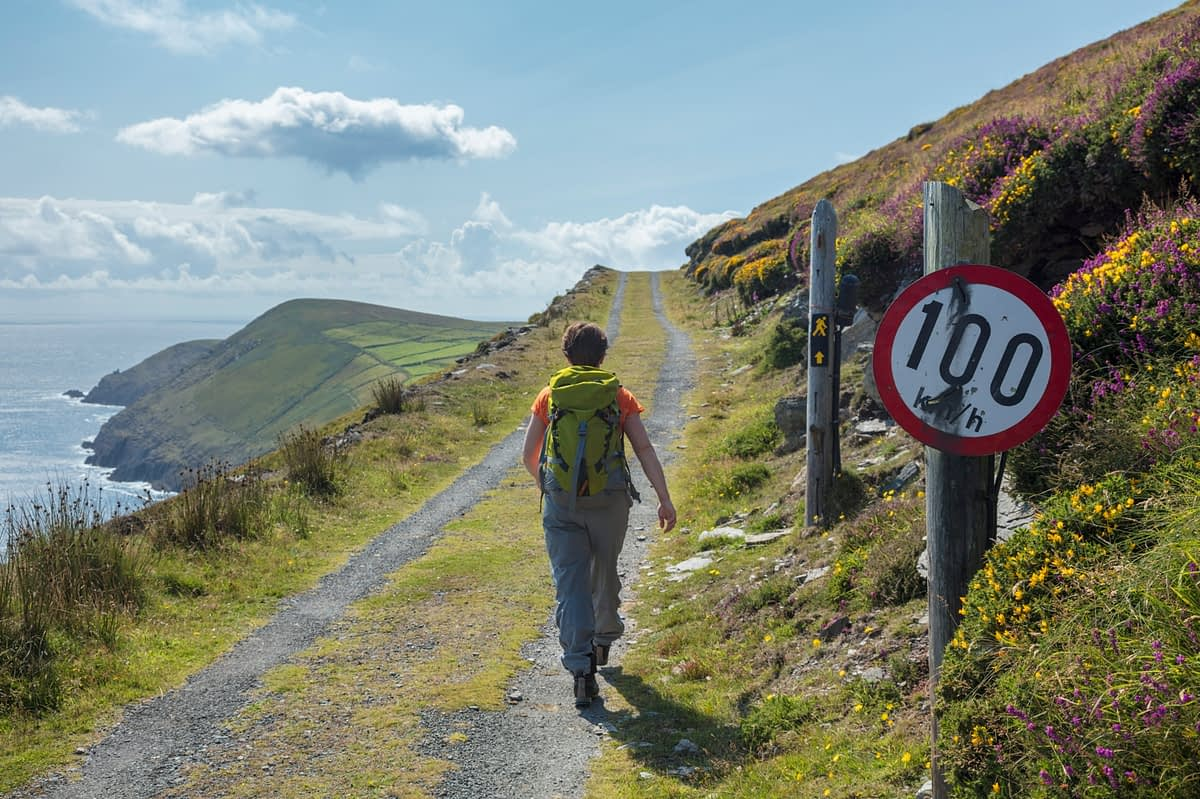 Hiker and quirky speed sign, Dursey Island, Beara Peninsula, County Cork, Ireland.