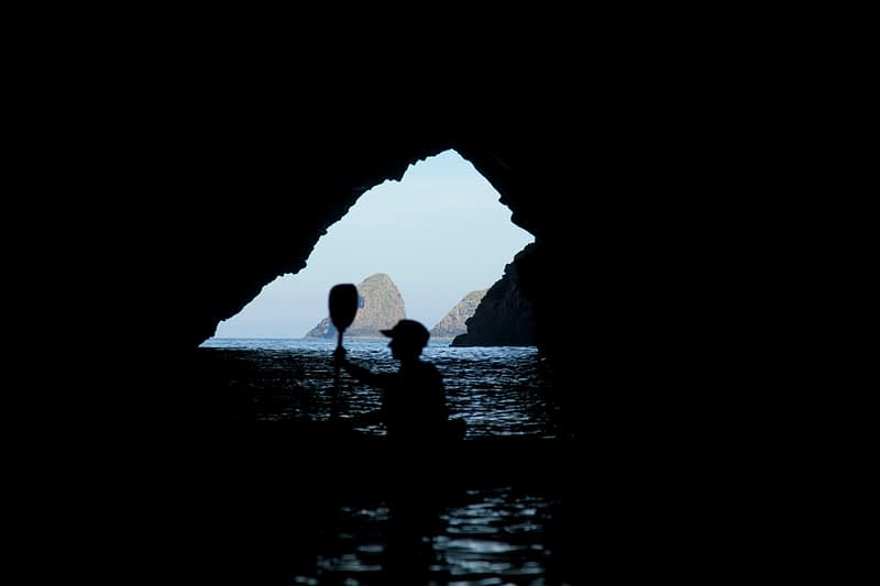 Sea kayaker silhouetted in the mouth of a cave, North Mayo seacliffs, Co Mayo, Ireland.