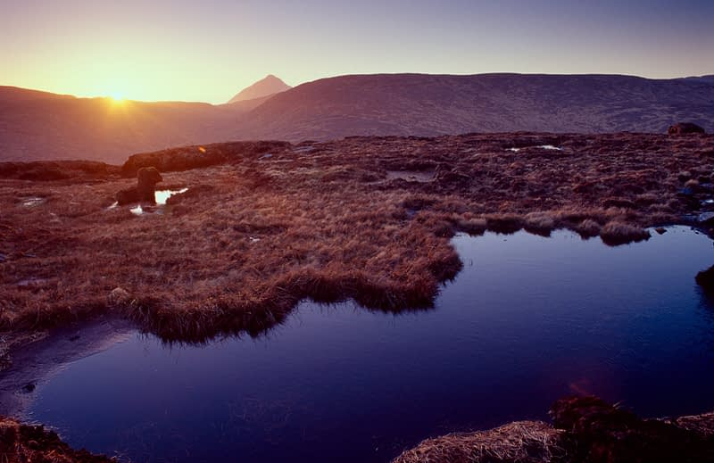 Sun setting behind Errigal and the Derryveagh Mountains from Farscallop, Co Donegal, Ireland.