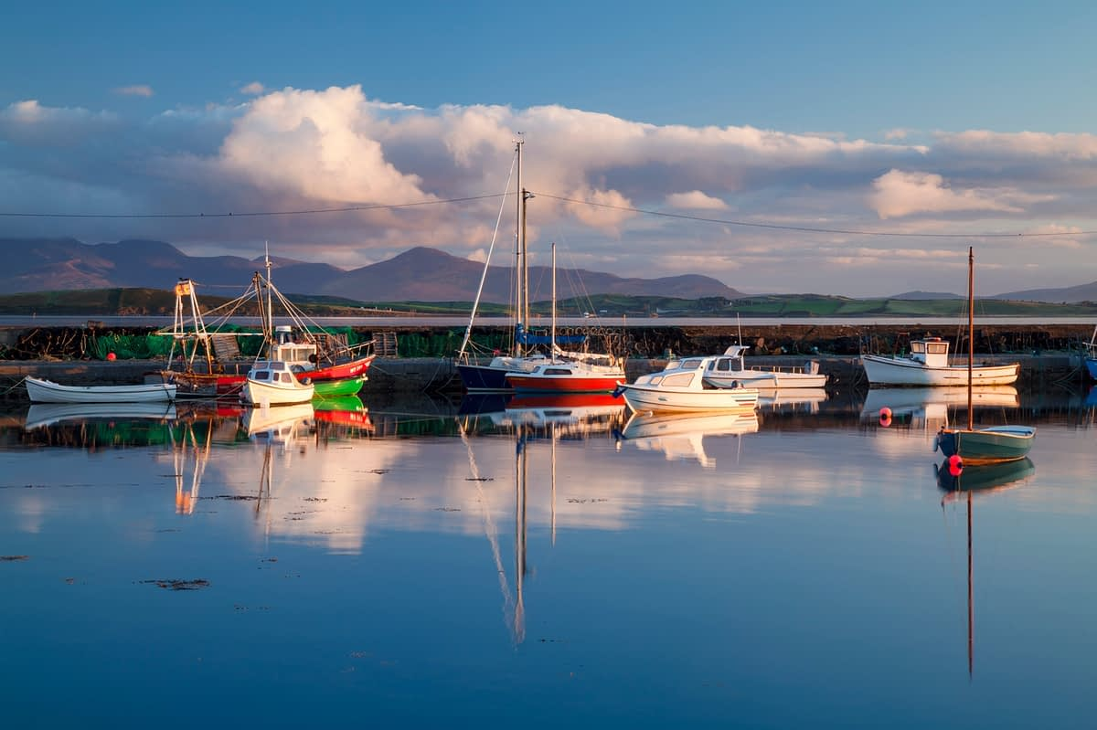 Evening reflection of fishing boats in Murrisk harbour, Clew Bay, County Mayo, Ireland.