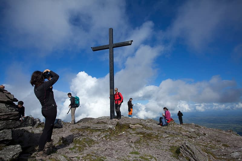 Walkers at the summit of Carrauntoohil, Ireland's highest mountain, MacGillycuddy's Reeks, County Kerry, Ireland.