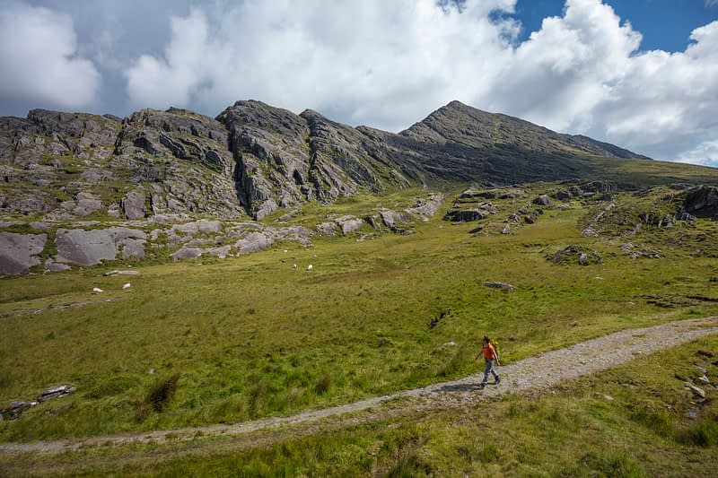 Hiker beneath the southwest ridge of Hungry Hill, Beara Peninsula, County Cork, Ireland.