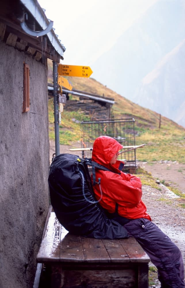 Walker sheltering from the rain, Tour of Mont Blanc, Val Ferret, Switzerland.