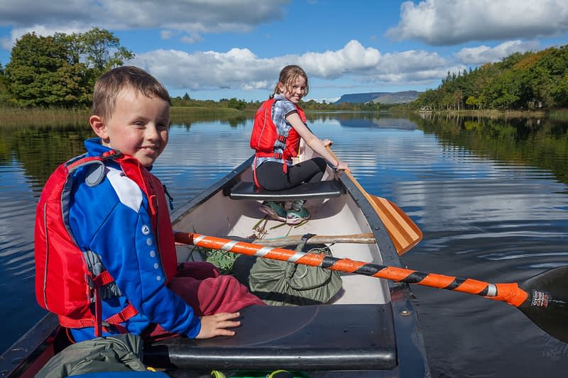 Family canoeing the Garavogue River to Lough Gill, Sligo town, County Sligo, Ireland.