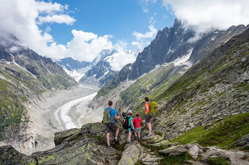 Hiking family above Mer de Glace glacier, Chamonix Valley, French Alps, France.