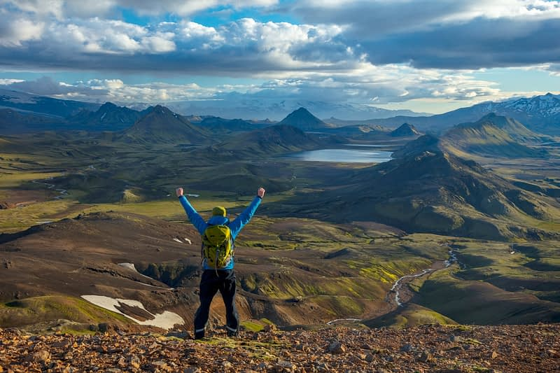 Hiker looking over the mountains and lake at Alftavatn, from Jokultungur on the Laugavegur hiking trail. Central Highlands, Sudhurland, Iceland.