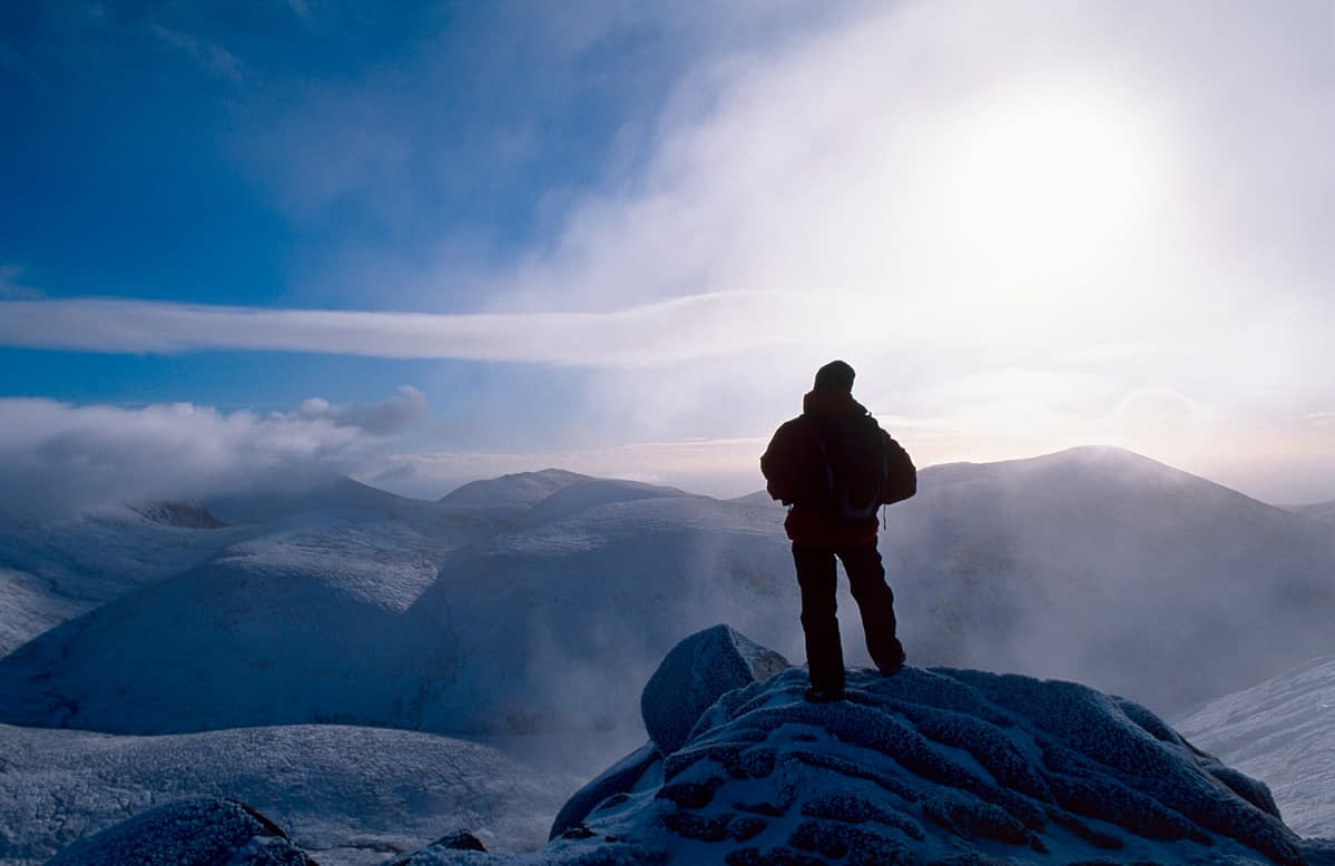 Winter walker at the summit of Slieve Bearnagh, Mourne Mountains, Co Down, Northern Ireland.