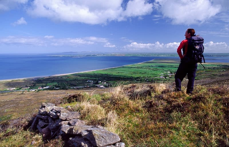 Walker looking over Tralee Bay from the Slieve Mish Mountains, Co Kerry, Ireland.